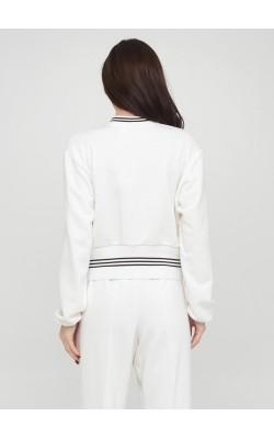 Біла трикотажна кофта з манжетами на блискавці